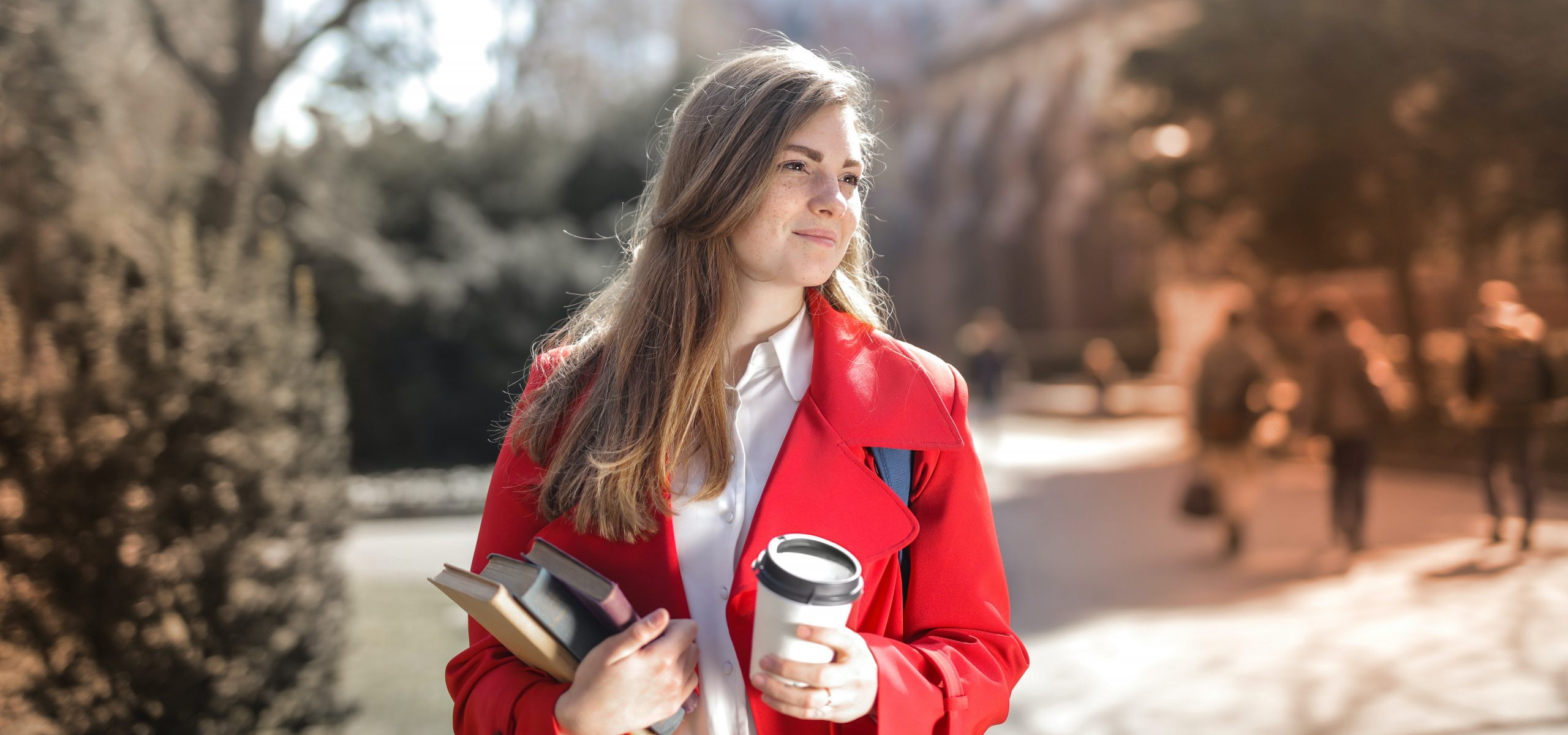 Woman wearing red coat, holding book and coffee as she walsk through university grounds