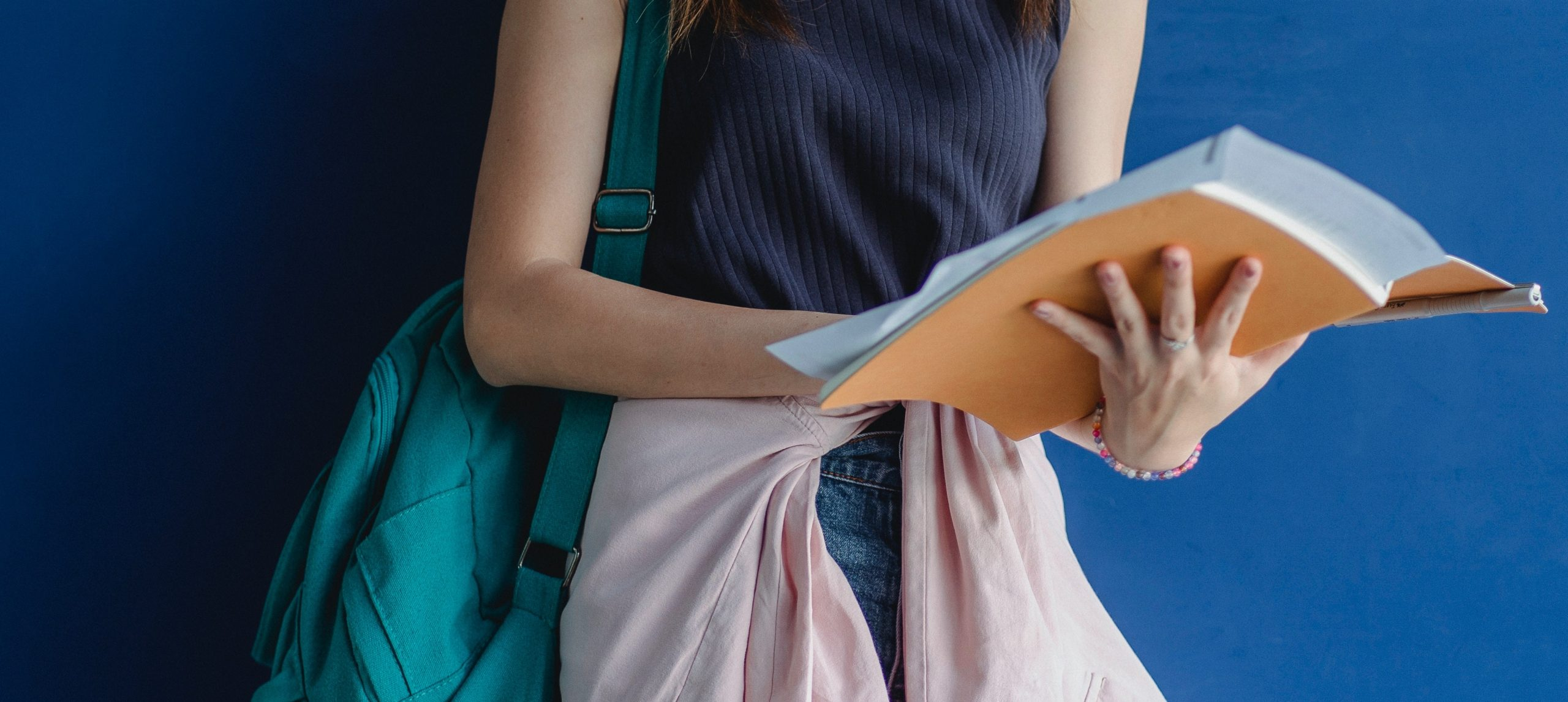 Woman holding book with backpack on shoulder