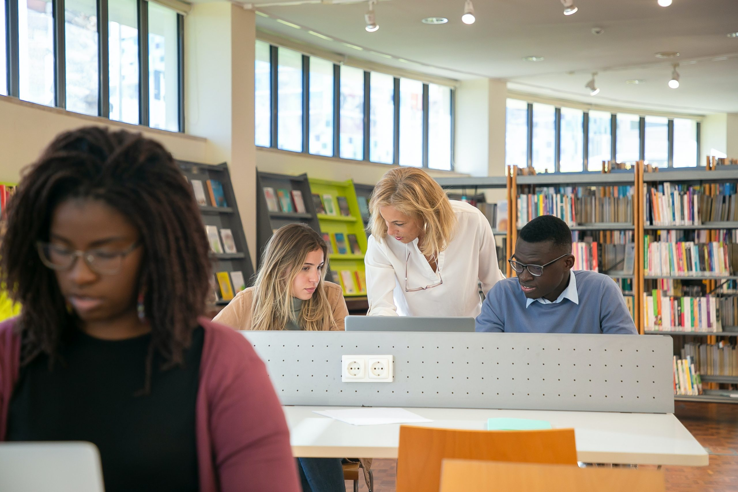 Lady helping students in library